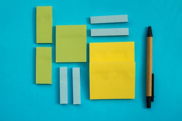 Na niebieskiej ścianie umieszczone są naklejki o różnych rozmiarach i kolorach. obok jest długopis. notesy na notatki i przypomnienia. płaska linia.