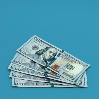 Na niebieskim polu rozłożył się plik stu dolarów gotówki. miejsce na etykietę, makietę, makietę.