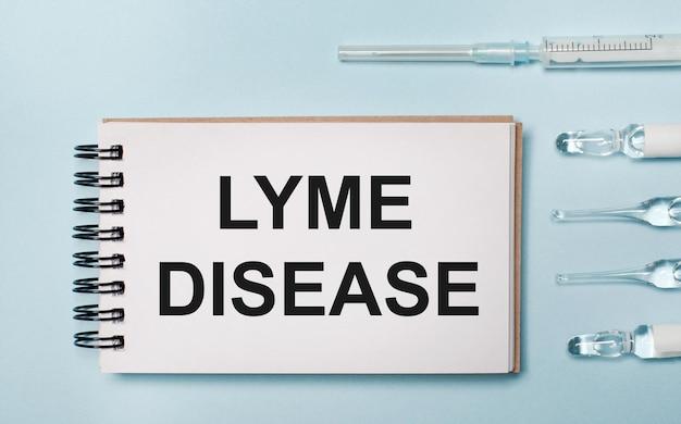 Na niebieskim tle ampułka z lekami i notes z napisem lyme disease. koncepcja medyczna