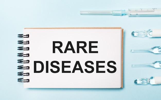 Na niebieskim tle ampułka z lekami i notes z napisem rzadkie choroby. koncepcja medyczna