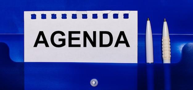 Na niebieskim tle białe długopisy i kartka z napisem agenda