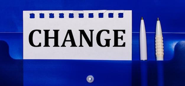 Na niebieskim tle białe długopisy i kartka z napisem zmień