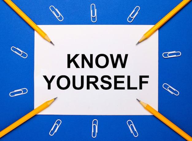 Na niebieskim tle białe spinacze do papieru, żółte ołówki i biała kartka papieru z napisem poznaj siebie