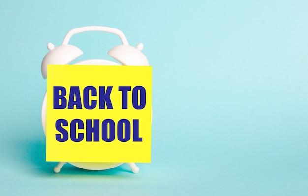Na niebieskim tle - biały budzik z żółtą naklejką na notatki z napisem back to school.