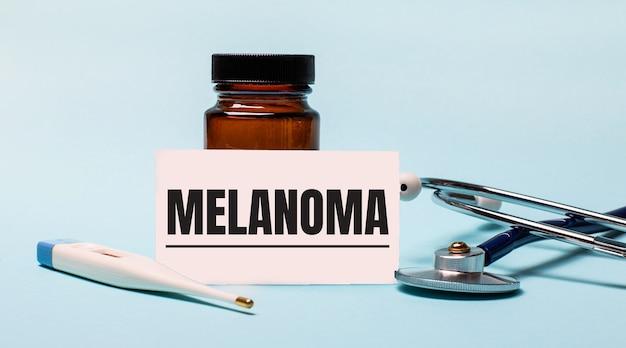 Na niebieskim tle - buteleczka na tabletki, stetoskop, termometr elektroniczny i karteczka z napisem melanoma