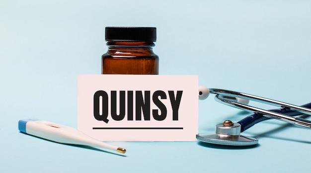 Na niebieskim tle - butelka na tabletki, stetoskop, termometr elektroniczny oraz kartka z napisem quinsy. koncepcja medyczna