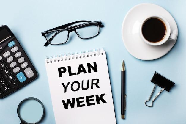 Na niebieskim tle okulary, kalkulator, kawa, lupa, długopis i notatnik z napisem zaplanuj swój tydzień