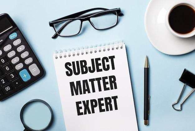 Na niebieskim tle okulary, kalkulator, kawa, lupa, długopis i notes z napisem temat eksperta
