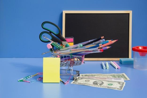 Na niebieskim tle wózek z długopisami z pisakami ołówkowymi, z tyłu tablica