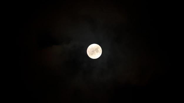 Na nocnym niebie księżyc z chmurami. zdjęcie wysokiej jakości