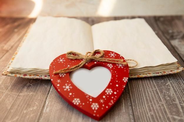 Na notebooku leży czerwona ramka w kształcie serca