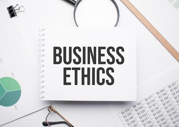 Na notesie do pisania tekstu etyka biznesowa, lupa,tabele i okulary.