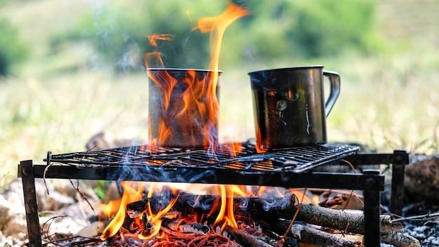 Na ognisku gotuje się woda w dwóch blaszanych kubkach