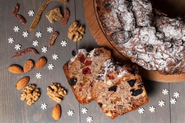Na okrągłym drewnianym talerzu leży świąteczna babeczka z owocami, orzechami i przyprawami. w pobliżu znajdują się dwa kawałki ciasta. na szarym stole rozrzucone są białe gwiazdki, orzechy i kandyzowane owoce. ciasto świąteczne.