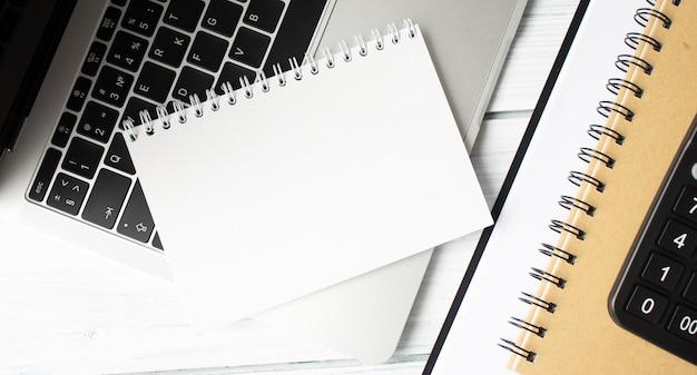 Na otwartym laptopie leży pusty notatnik. miejsce na tekst.