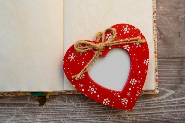 Na otwartym notatniku leży czerwona ramka w kształcie serca