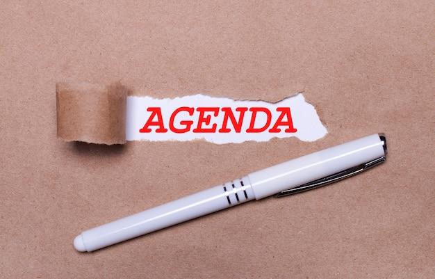 Na papierze kraft biały długopis i biały pasek papieru z napisem agenda.