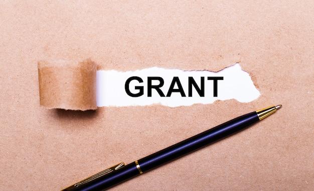 Na papierze kraft biały długopis i biały pasek papieru z napisem grant.