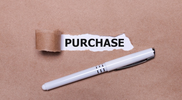 Na papierze kraft biały długopis i biały pasek papieru z napisem kup.