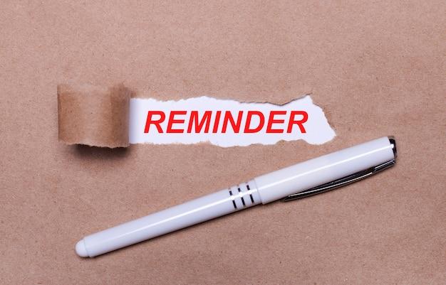 Na papierze kraft biały długopis i biały pasek papieru z napisem przypomnienie.