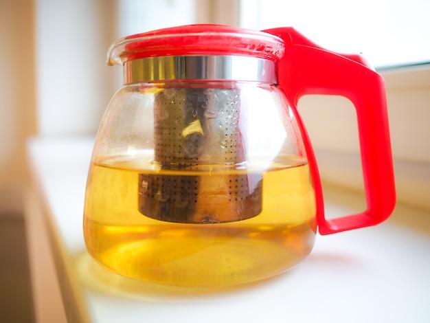Na parapecie stoi przezroczysty szklany czajniczek. proces parzenia zielonej herbaty lub herbaty ziołowej. smakowy zdrowy napój dla zdrowego stylu życia.