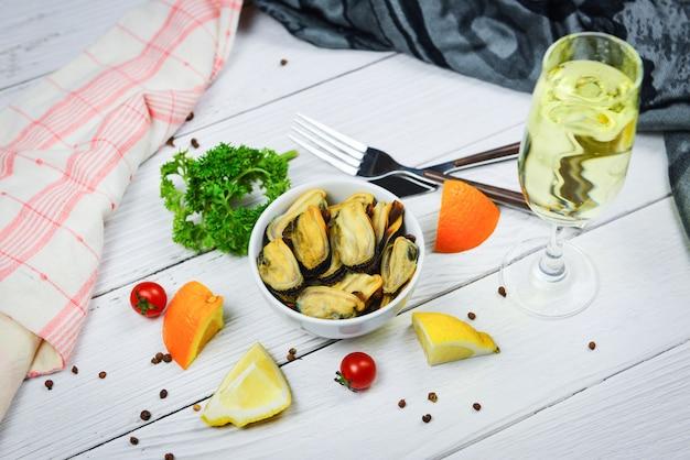 Na parze małże i kieliszek do wina podawane w sosie z miski z owocami morza, pyszne w restauracji na stole