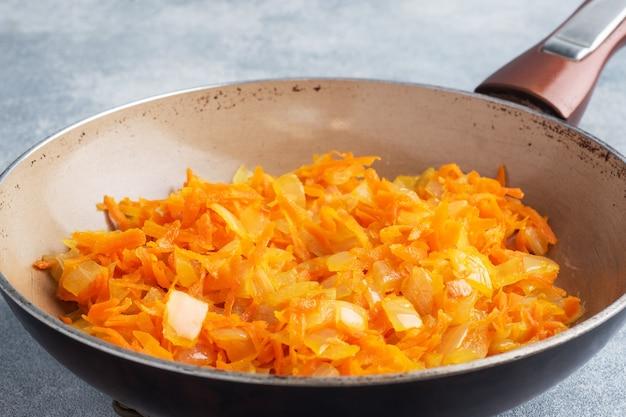 Na patelni usmażyć startą marchewkę i posiekaną cebulę na oleju. szary beton.