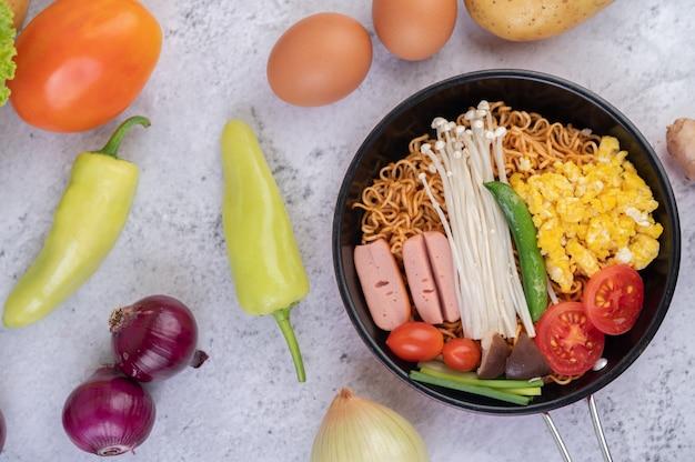 Na patelni wymieszaj smażony makaron, który łączy kukurydzę, złoty igłowy grzyb, pomidor, kiełbasę, edamame i dymkę.