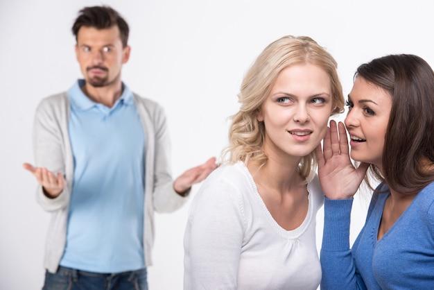 Na pierwszym planie dziewczyny plotkują. za zaskoczonym mężczyzną.