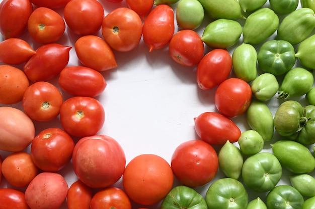 Na pierwszym planie optymalne zielone i czerwone pomidory.