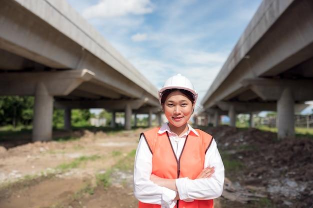Na placu budowy pewna siebie pracownica budowlana pozuje do portretu.