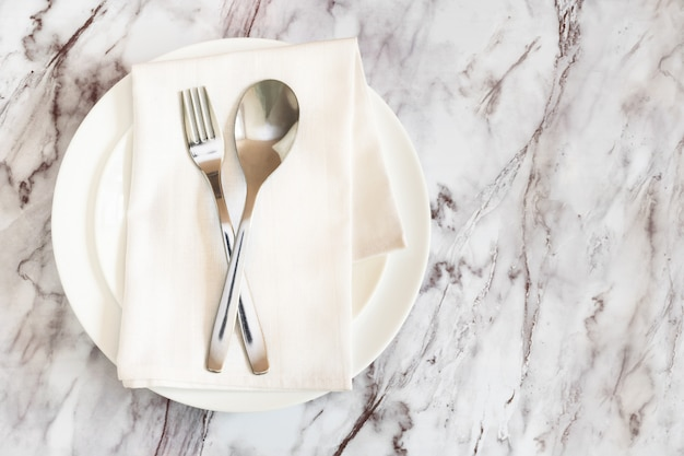 Na płasko leżą sztućce, widelec i nóż na serwetce na pustym białym talerzu na marmurowym stole.