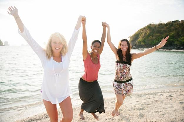 Na plaży bawi się grupa różnych osób?