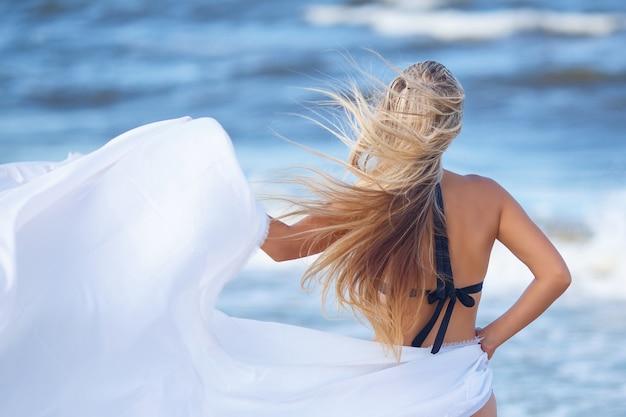 Na plaży blondynka stoi z tyłu, koncepcja odpoczynku i relaksu