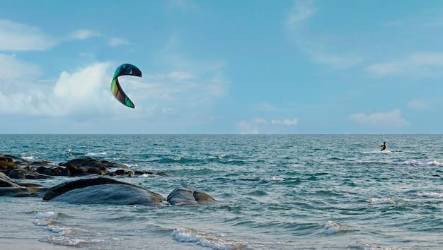 Na plaży jest windsurfing. podążając za morską bryzą