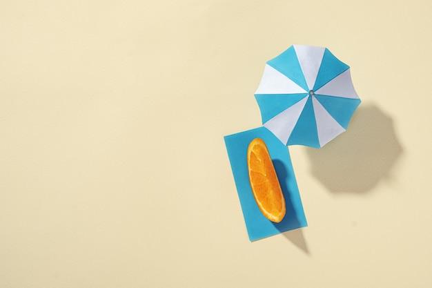 Na plaży parasol jako ochrona przed słońcem i kawałek pomarańczy na ręczniku w postaci osoby wypoczywającej i opalającej się - papierowa oprawa i koncepcja relaksu nad morzem.