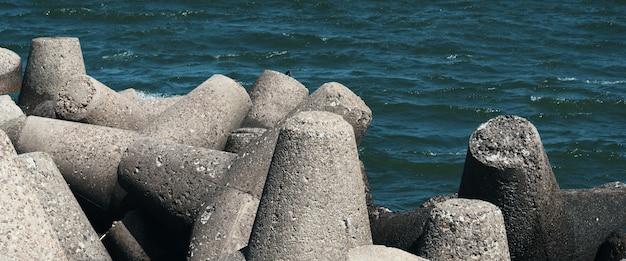 Na plaży przed falami leżą duże kamienie.