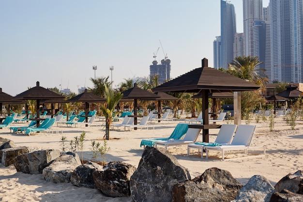 Na plaży stoją białe leżaki pod brązowymi drewnianymi parasolami