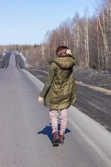 Na poboczu idzie młoda kobieta. droga w lesie.