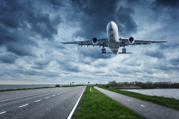 Na pochmurnym niebie leci samolot pasażerski