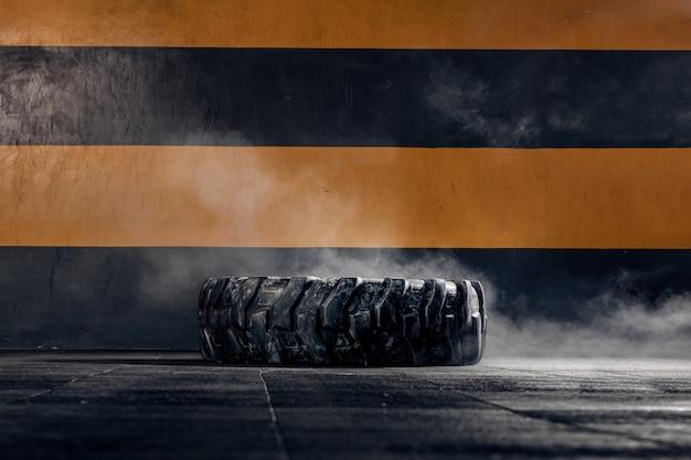 Na podłodze sali gimnastycznej leży duże koło traktora do crossfitu. wyposażenie sportowe