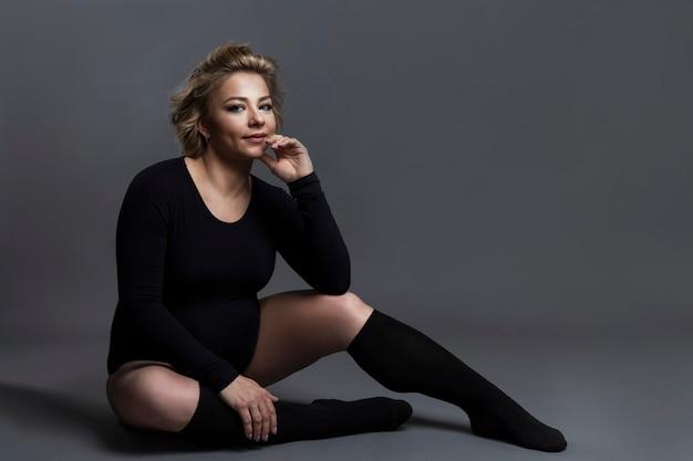 Na podłodze siedzi piękna kobieta w ciąży w czarnym body i legginsach. tajemniczy stan w oczekiwaniu na dziecko. szare tło. miejsce na tekst.