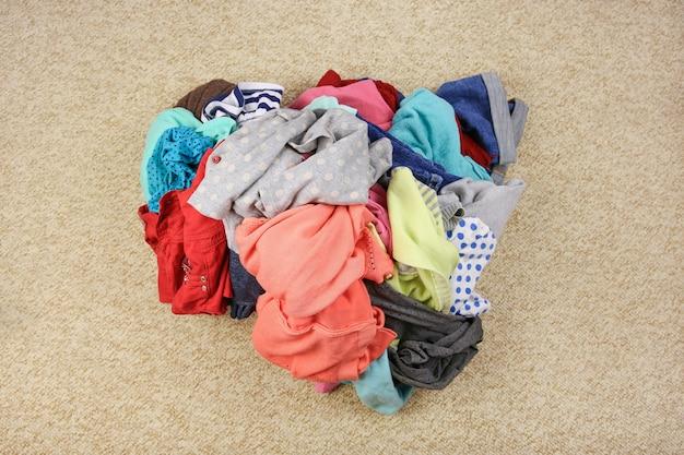 Na podłodze stos niedbale porozrzucanych ubrań. widok z góry.