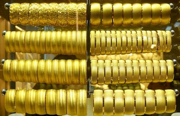 Na podstawkach wiszą złote bransoletki z biżuterią
