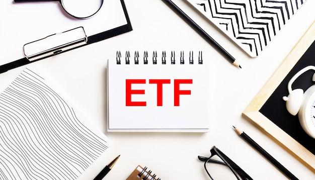Na podświetlanym stoliku znajdują się zeszyty, szkło powiększające, budzik, okulary i długopis. a pośrodku znajduje się notatnik z tekstem etf exchange traded funds