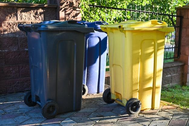 Na podwórku znajdują się trzy kosze na odpady zmieszane