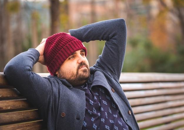 Na pokład facet w wełnianym kapeluszu i swetrze siedzi na ławce w parku relaksując się