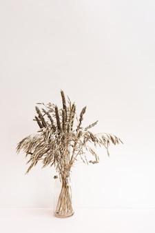 Na polu suszone kłoski i zioła w wazonach na jasnoróżowym tle.