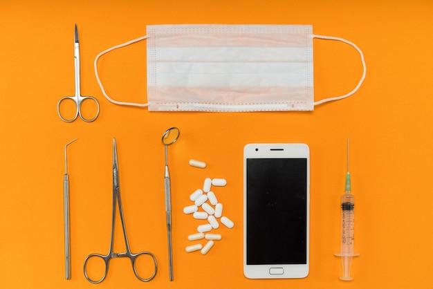 Na pomarańczowej powierzchni znajduje się smartfon, strzykawka, pigułki, instrumenty dentystyczne i maska na twarz
