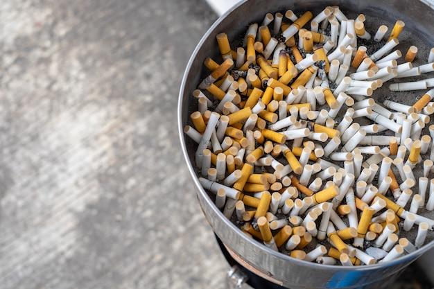 Na popielniczce znajduje się wiele rodzajów niedopałków papierosów. papieros nie jest dobry dla zdrowia.
